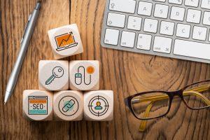 Online-Marketing Komponenten als Symbole auf Würfeln am Arbeitsplatz